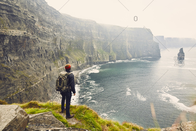Man looking at Irish coastal cliffs