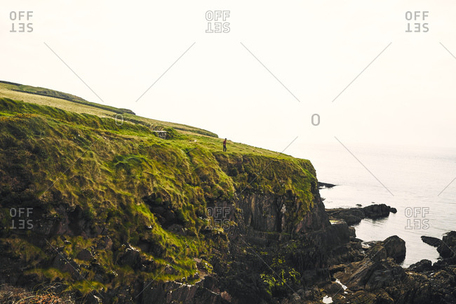 Man standing at Irish coastal cliffs