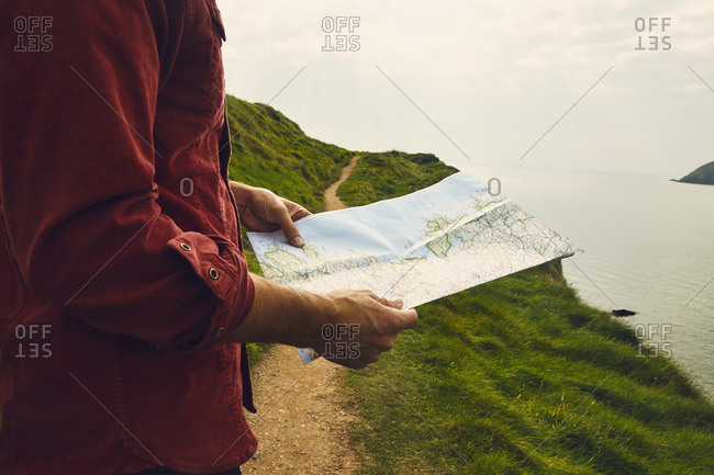 Map in man's hands by sea