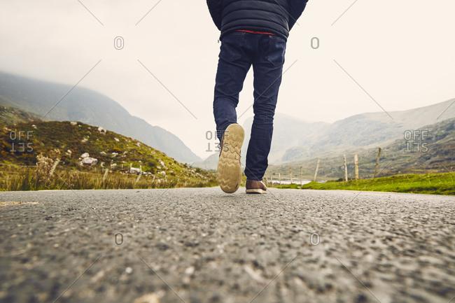 Legs of man on rural road