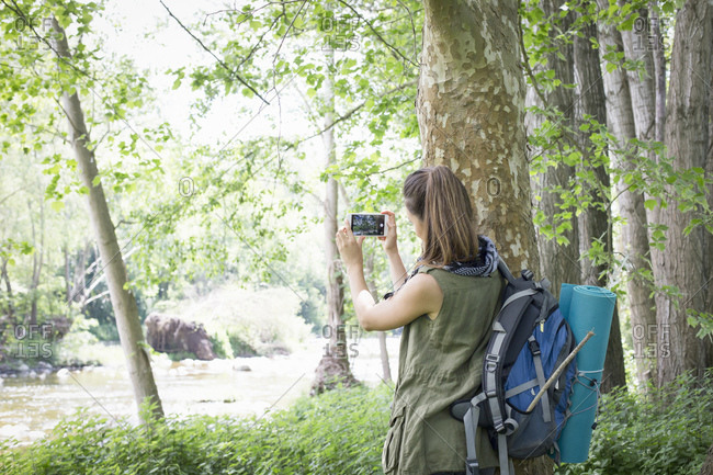 Woman taking photo against a tree