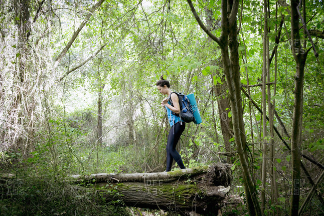 Woman walking on log in forest setting