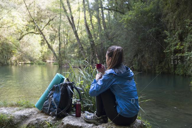 Woman enjoying coffee by a river