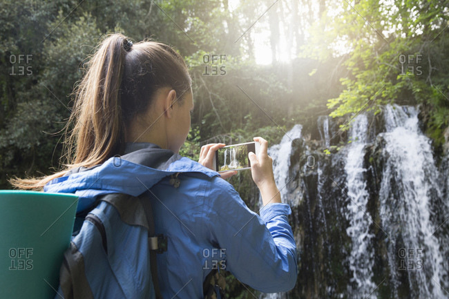 Woman taking photo of a waterfall