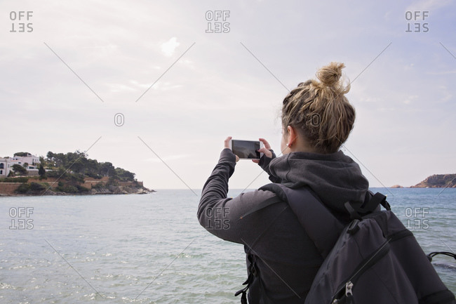 Woman taking photo of an island