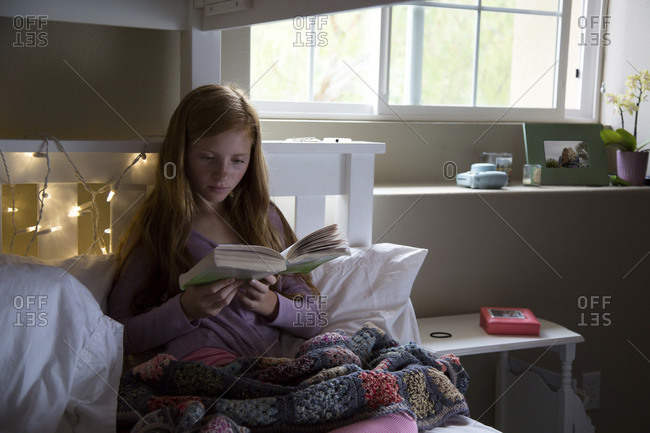 Girl on a bunk bed reading book