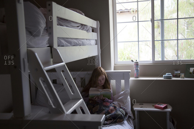 Girl on bunk bed reading a book
