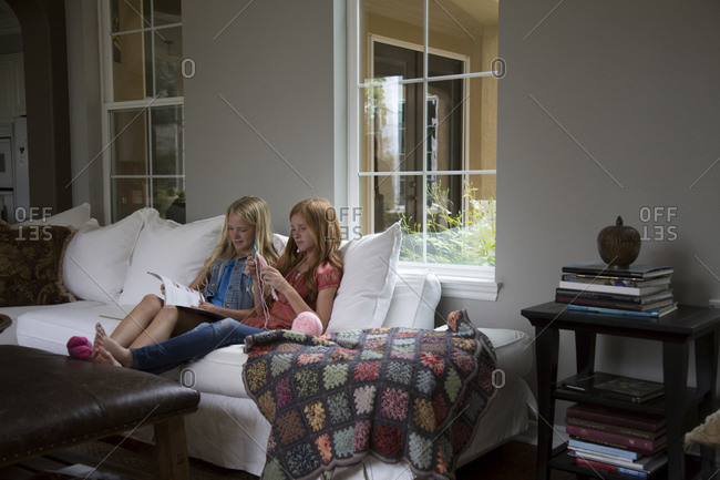 Girls reading book and knitting