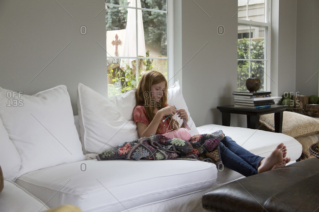 Girl sitting on couch knitting