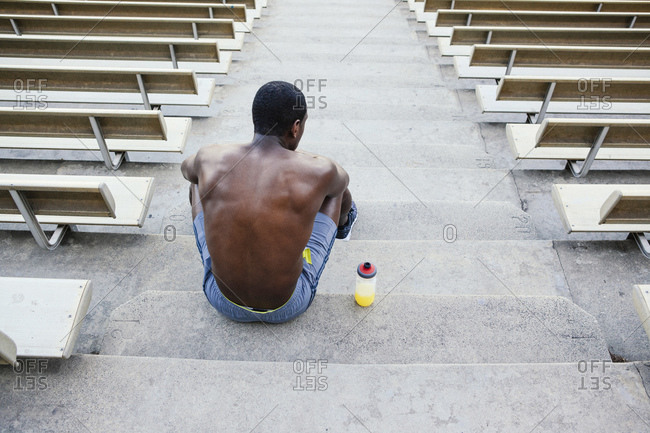 Male athlete sitting on stadium stairs