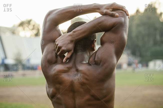 Male athlete stretching his arms