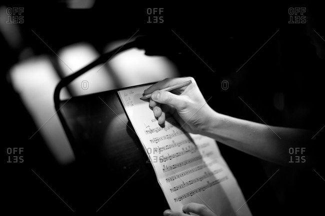 Musician writing on sheet music on a music stand