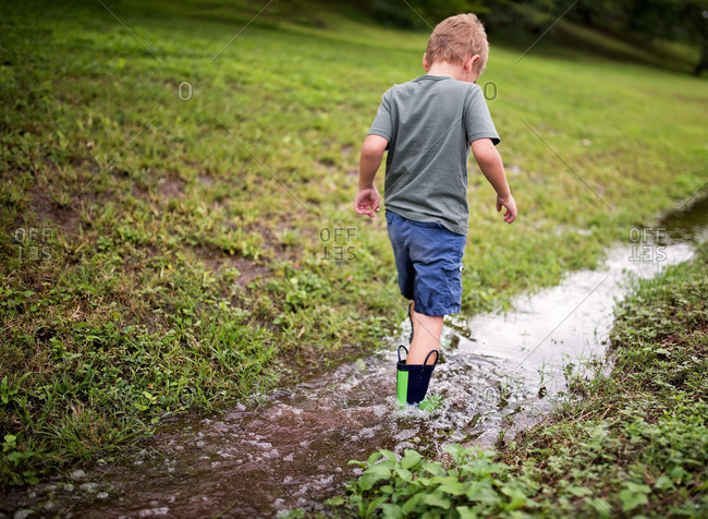 Boy playing in a ditch after a rain storm