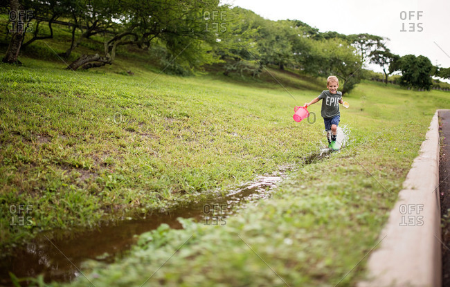 Boy running in a ditch after a rain storm