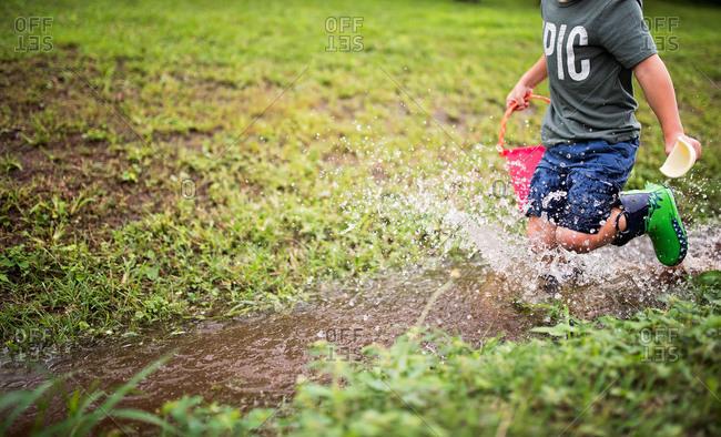 Boy splashing in a ditch after a rain storm