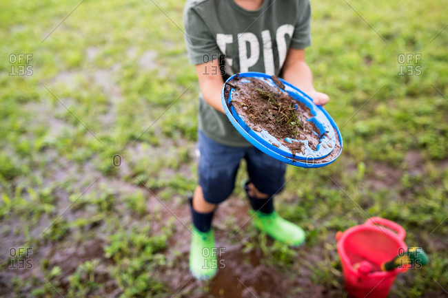 Boy making mud pies after a rain storm