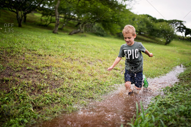 Boy playing in a flooded ditch