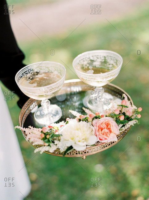 Server carrying tray with antique champagne glasses and flowers