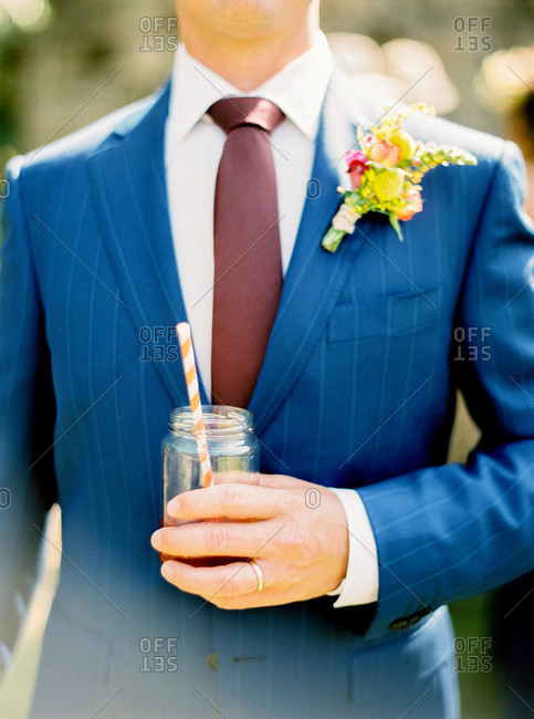 Man in blue suit holding drink in mason jar