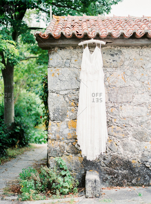 White gown hanging from terracotta roof of old stone building