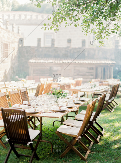Tables set in garden for outdoor wedding reception