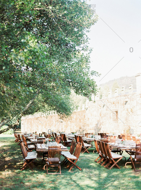 Tables set in garden of stone castle for outdoor wedding reception