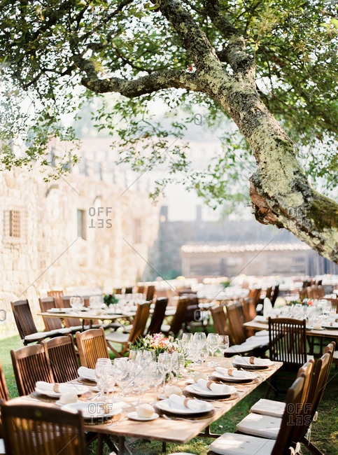 Wedding reception tables set under tree in garden of stone castle