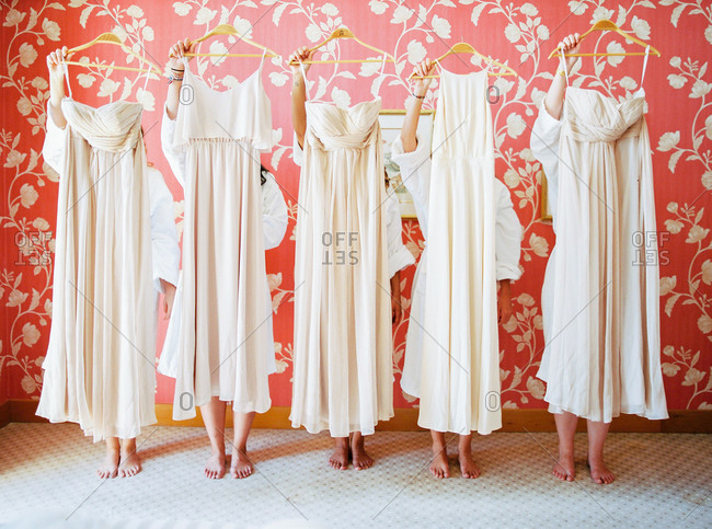 Five bridesmaids holding their dresses up before flowered wallpaper