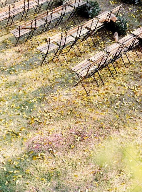Elevated view of rows of chairs in garden scattered with leaves