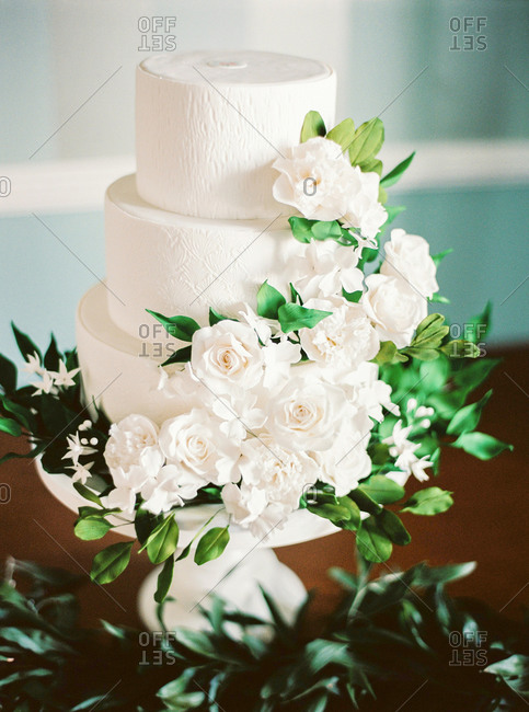 Wedding cake decorated with white flowers and green leaves