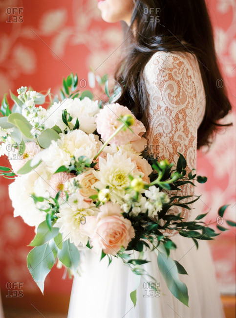 Bride holding wedding bouquet of pale pink and white flowers