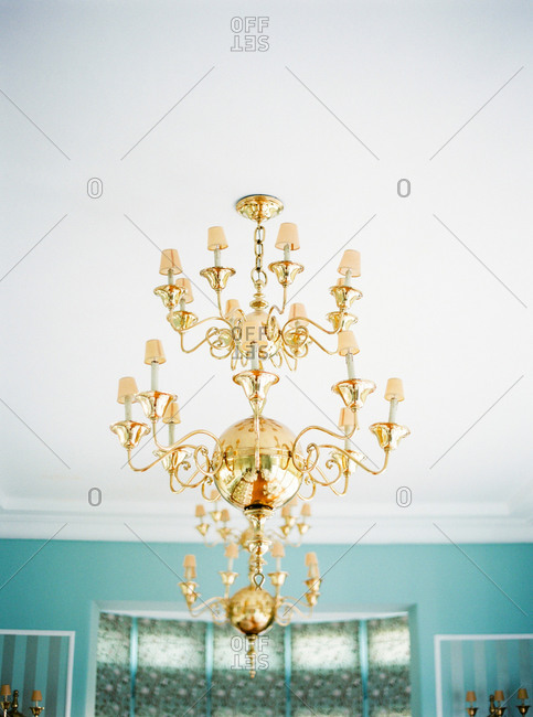 Brass chandeliers hanging from ceiling in blue room