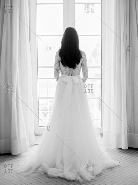 Back view of bride standing before window