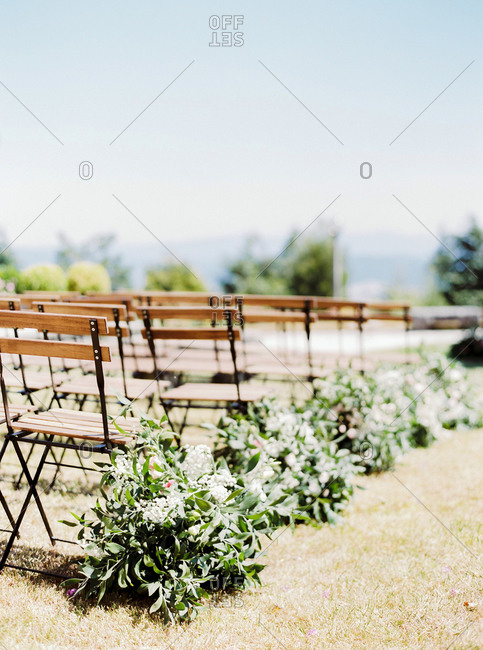 Chairs in sunny garden set for wedding ceremony