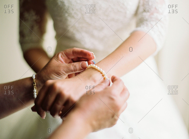 Woman fastening pearl bracelet around bride's wrist