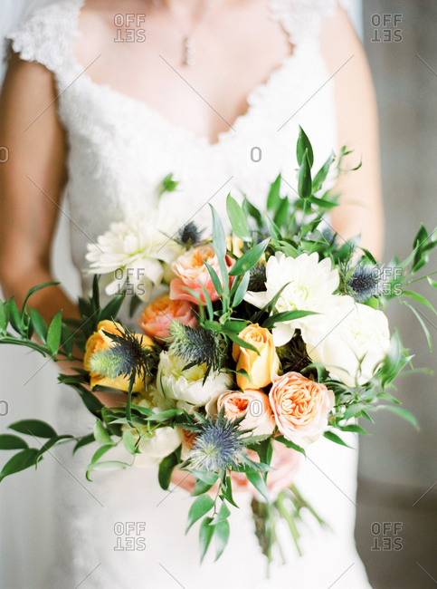 Bride holding wedding bouquet of yellow, pink and white flowers