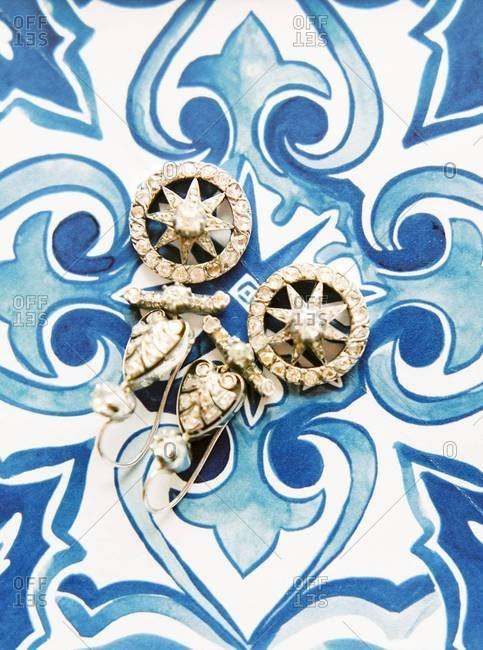 Overhead view of vintage earrings with star motif on tile background