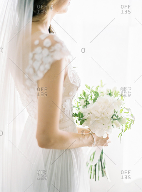 Side view of bride in elegant lace dress holding wedding bouquet