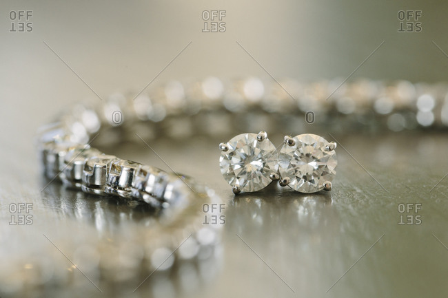Close-up of pair of diamond earrings and bracelet
