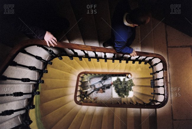 Overhead view of two men walking down spiral staircase