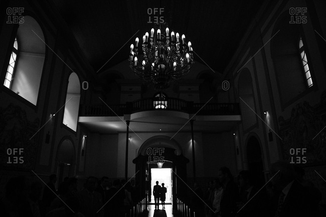 Back view of bride and groom silhouetted in church doorway