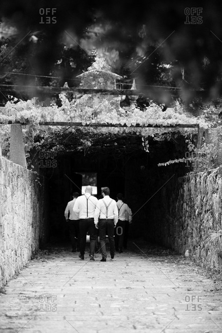 Group of men walking through stone walled tunnel