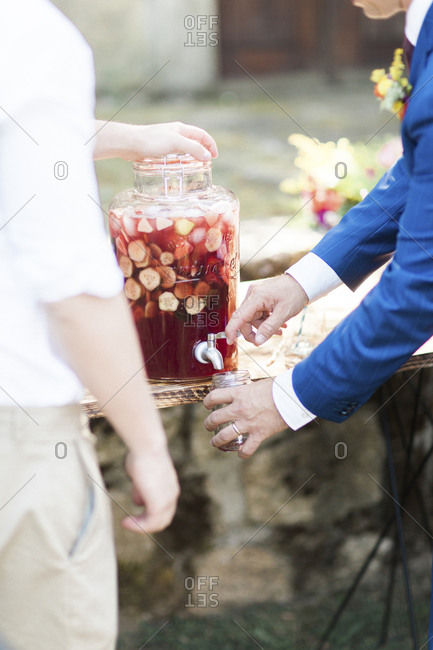 Man pouring glass of sangria from jug