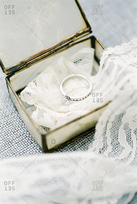 Overhead view of diamond ring in jewelry box with strand of lace