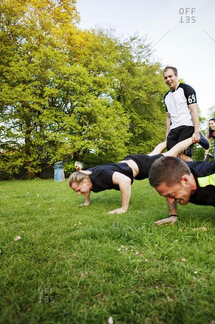 Men doing  wheelbarrow style pushups
