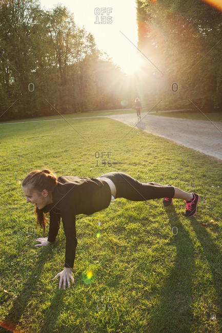 Woman doing pushups in a park at sunset