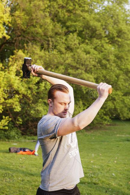Athletic man lifting a sledge hammer