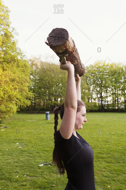 Athletic woman lifting a log in a park