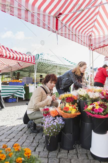 Women shopping for flowers in market flower shop