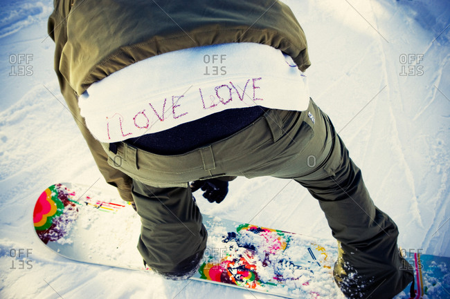 Snowboarder wearing clothing with a message about love